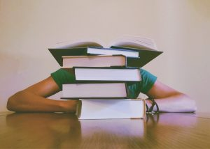 Students resting head on desk behind an intimidatingly large pile of textbooks